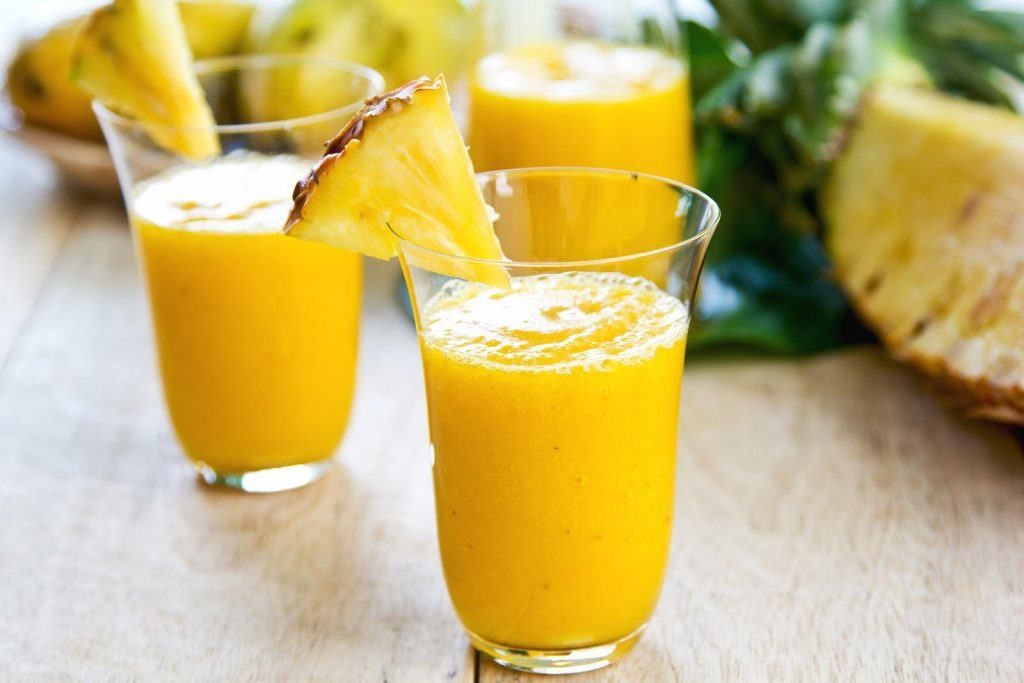 Mango with pineapple smoothie in jug and glasses