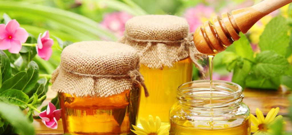 Honey in glass jars with flowers background.